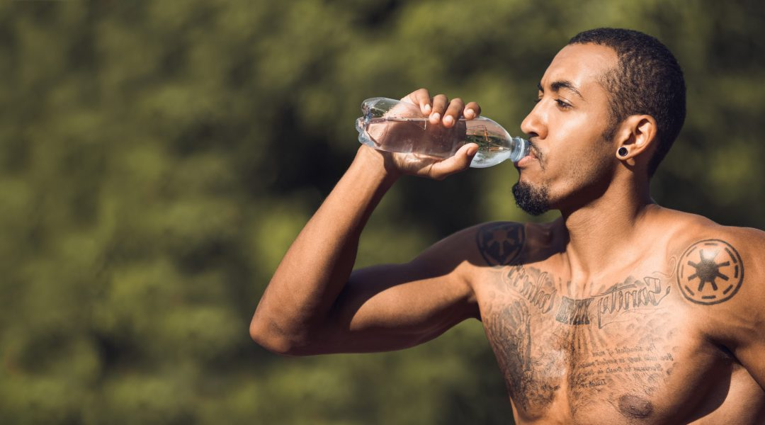 Shirtless Muscular Man Drinking Water After Training In Park, Free Space